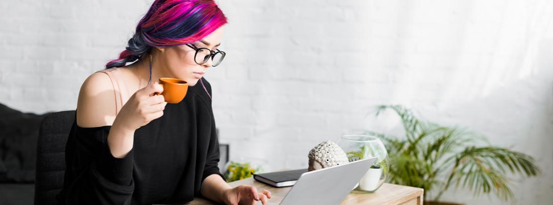 Mujer con una taza de café frente a un ordenador pidiendo cita previa en el SEPE