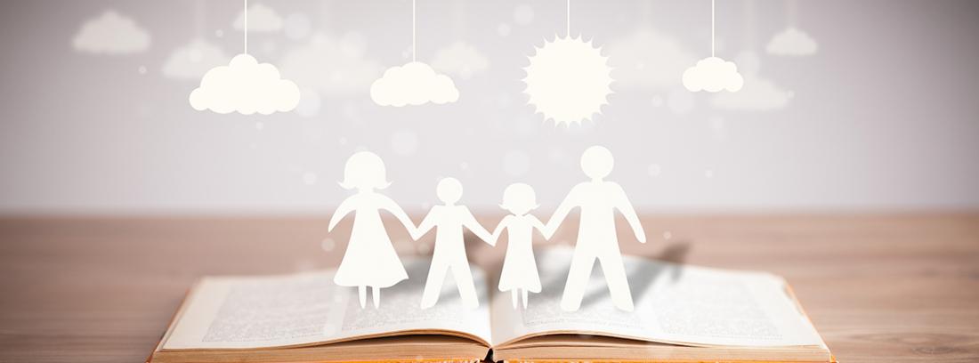 Figuras de cartón de una familia sobre un libro abierto