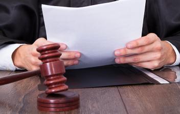 Juez en una mesa sujetando unos documentos