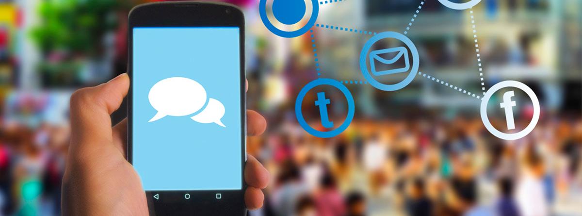 Manio sujetando un teléfono móvil con iconos de mensajes y apps