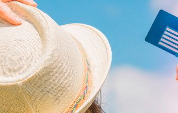 chica con sombrero sujetando una Tarjeta Sanitaria Europea