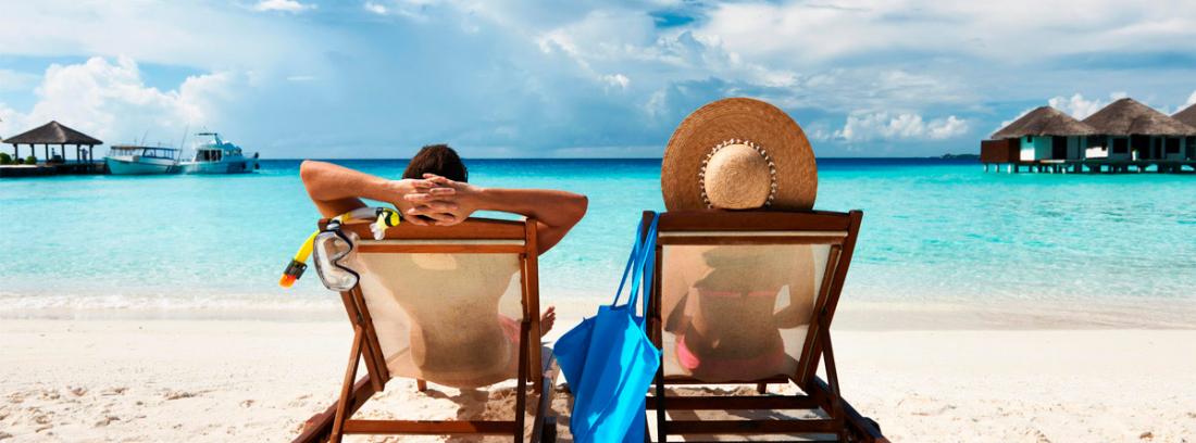 Hombre y mujer de espaldas sentados en tumbonas frente al mar