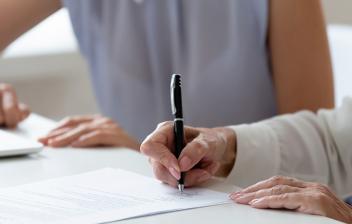 Mujer frente a un ordenador junto a otra mujer firmando un contrato de arras