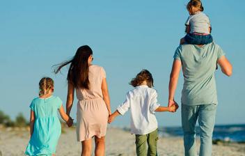 Dos adultos y tres niños caminando de espaldas por la playa