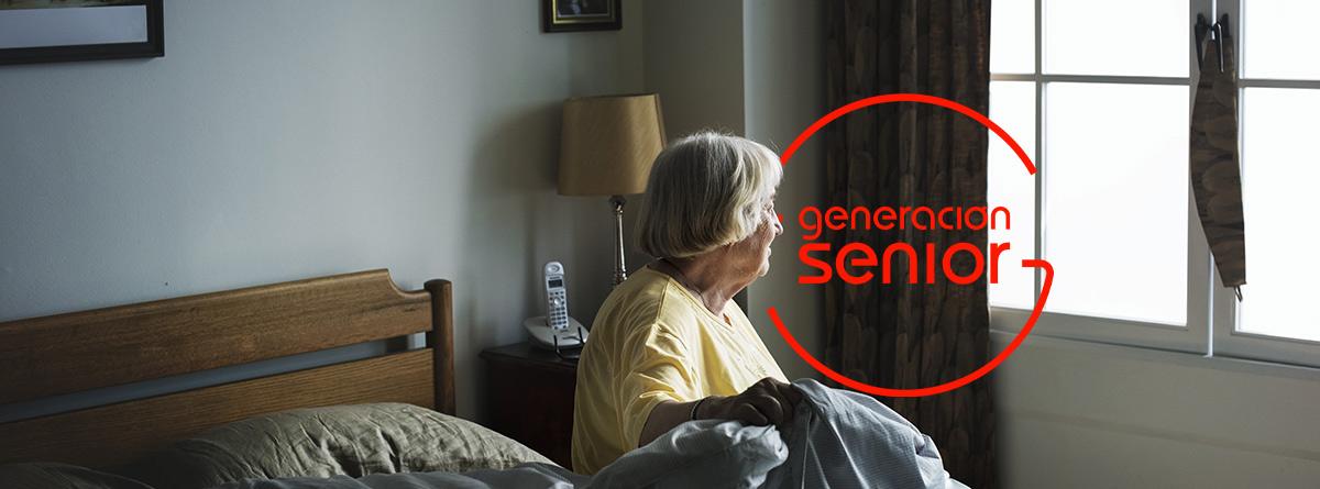 Mujer mayor sentada en una cama y mirando por una ventana