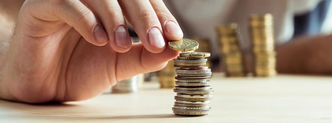hombre apilando monedas en una mesa