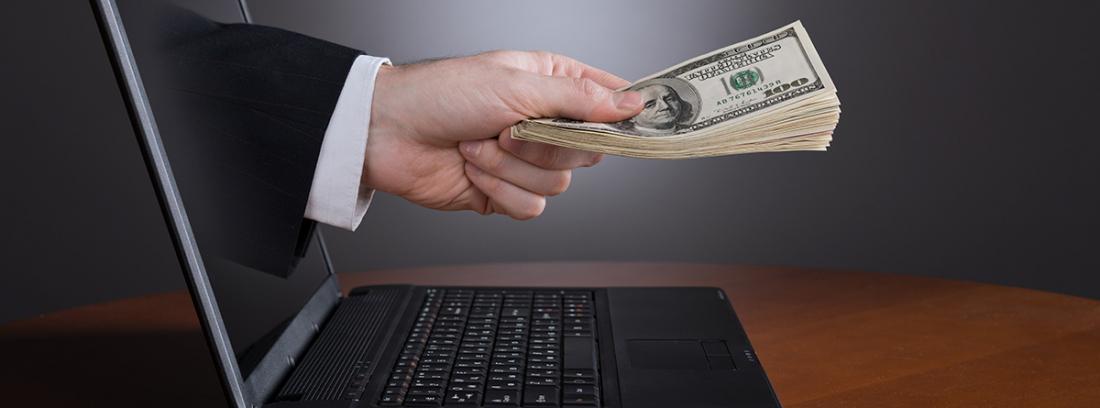 mano saliendo de la pantalla de un portátil con billetes