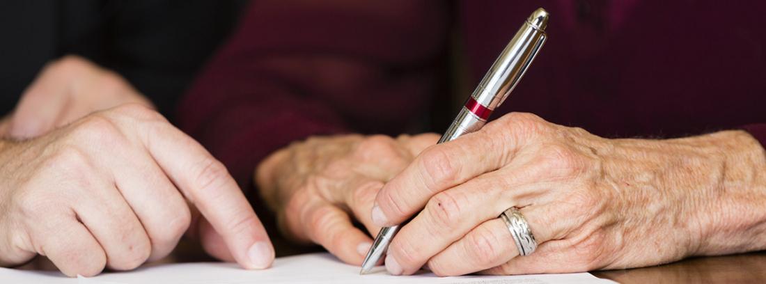 Unas manos sujetando un bolígrafo para firmar un documento