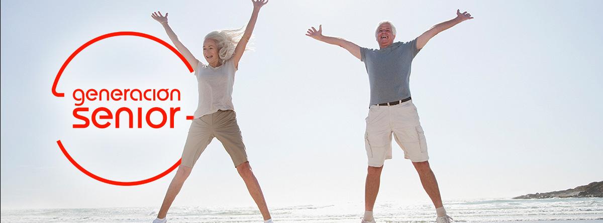 : Mujer y hombre mayores saltando en la playa