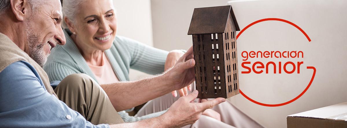 Hombre y mujer mayores con una maqueta de una casa