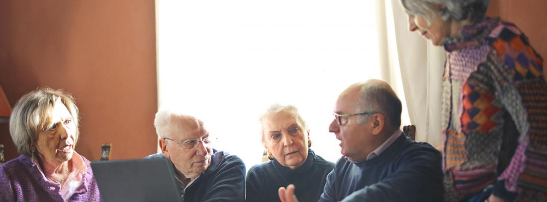 Ancianos hablando enfrente de una pantalla de ordenador
