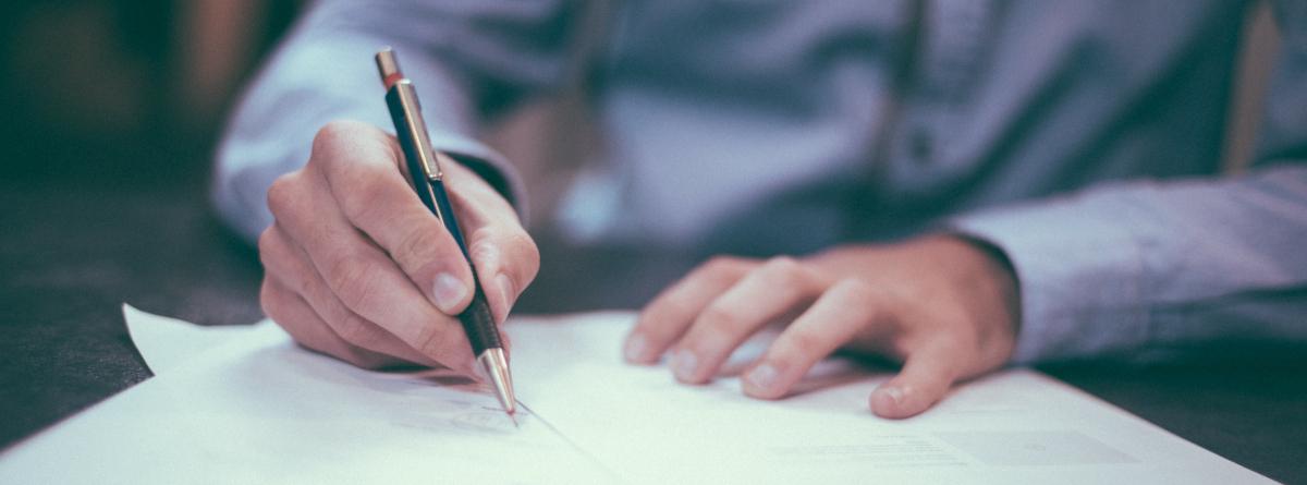 Un hombre firma un documento