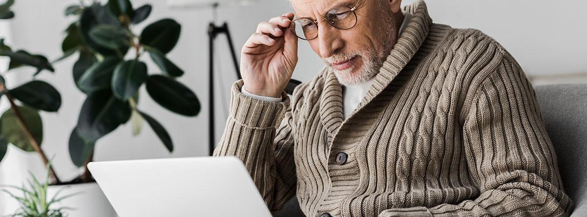 Hombre mayor sentado en un sillón con un portátil